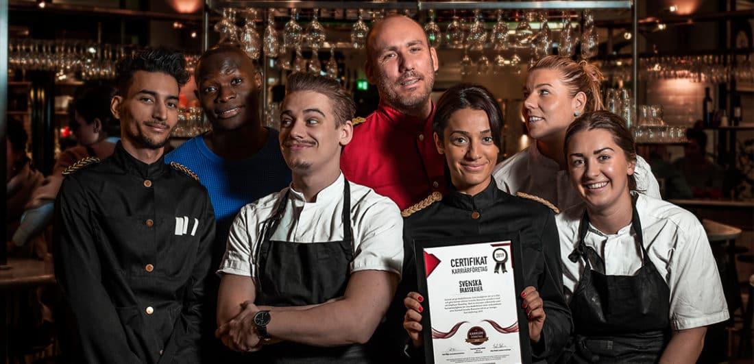 Medarbetare på Svenska Brasserier visar upp Karriärföretagens utmärkelse