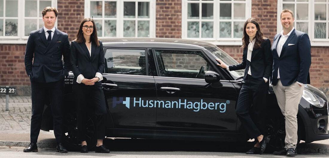 Fastighetsmäklare på HusmanHagberg framför bil